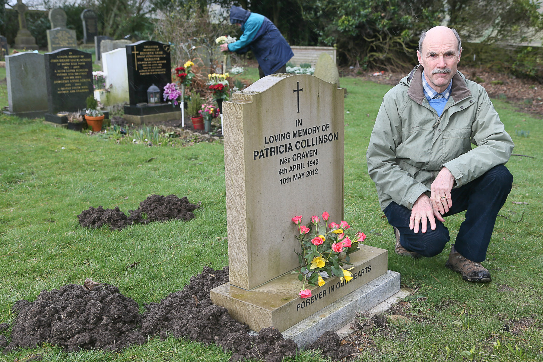 John Collinson at his wife's grave in Stanbury Cemetery, which is surrounded by molehills