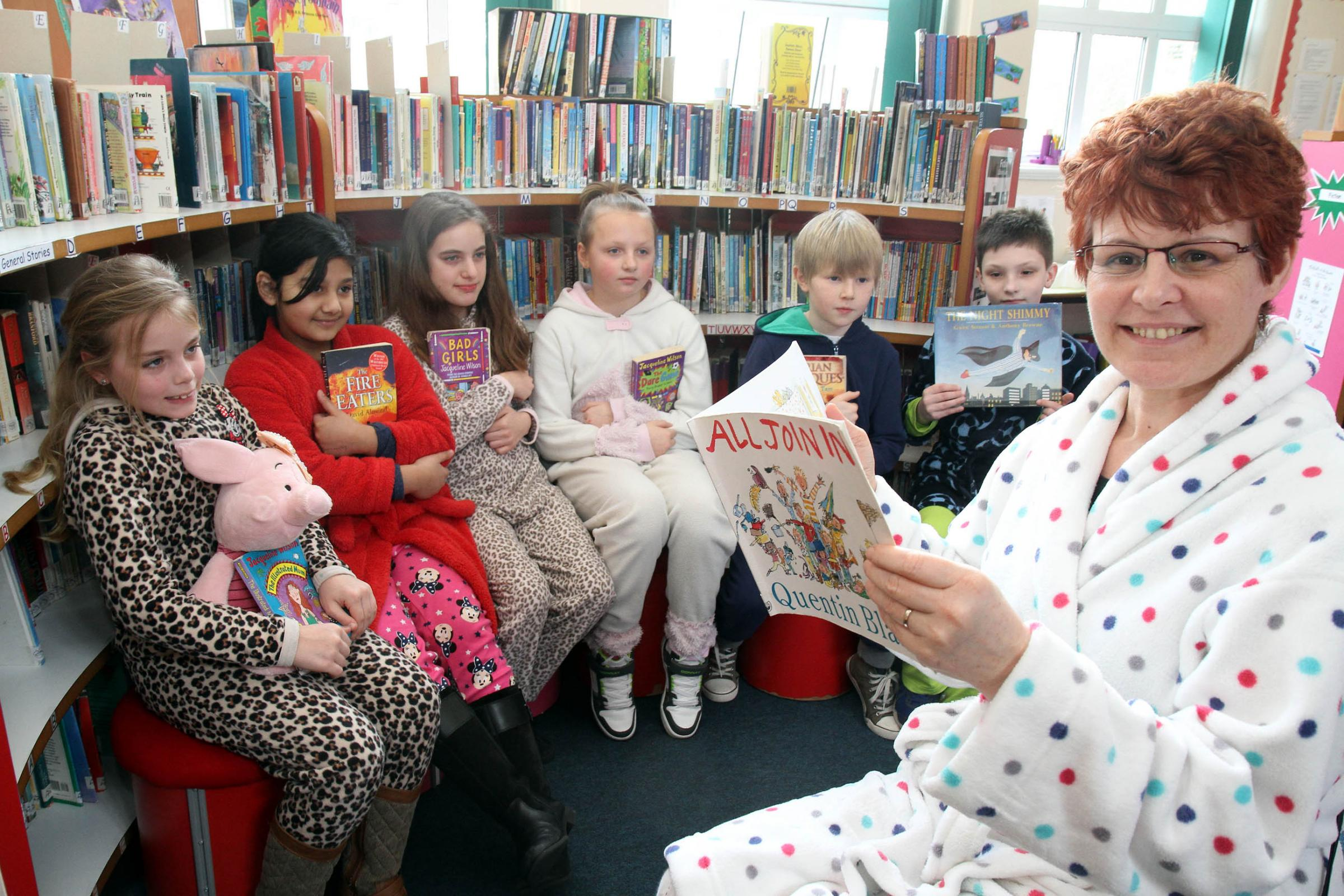Hothfield Junior School support assistant, Jane Spencer, joins pyjama-clad pupils for a book-reading session as part of efforts to raise vital funds for the Bradford Hospitals Children's Charity