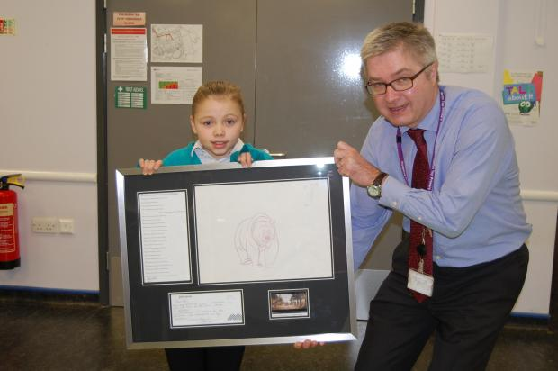 Merlin Top Primary Academy pupil, Page Wilson, and headteacher, Mike Harrison, with the framed illustration of the bear from the John Lewis Christmas advert
