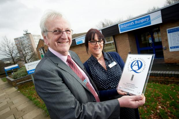 Ken Hargreaves, chairman of Holycroft Surgery's patient participation group, and Joanne Towers, the surgery's customer-services manager, with the Customer Service Excellence plaque