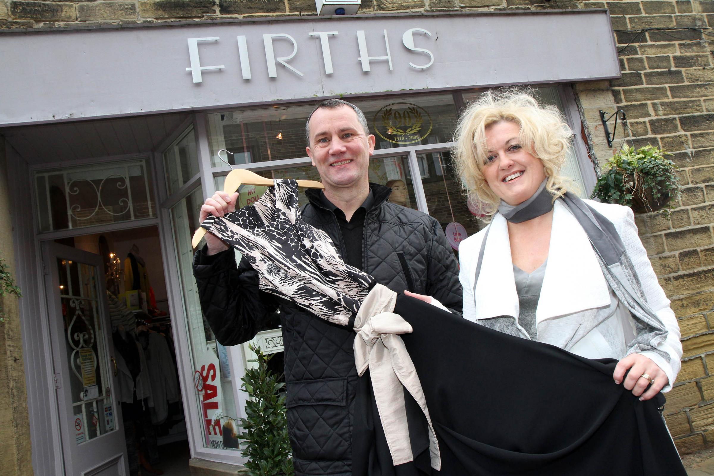 Councillor Glen Miller sizes up a dress for the fashion show, with the help of event organiser Nikki Carroll, owner of Firth's in Haworth