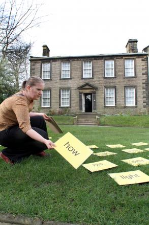 Bronte Parsonage Musuem arts officer Louisa Briggs is pictured laying out words on the museum lawn for the poetry session