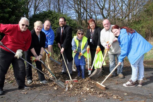 Keighley News: The clean-up squad tackles the grounds of the Rainbow Children's Centre