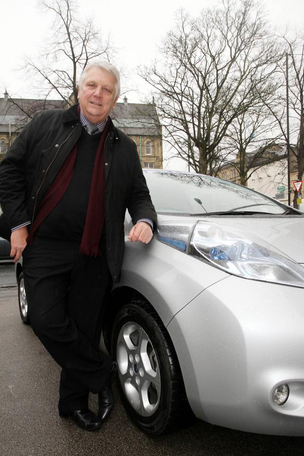 Keighley News: Private-hire boss Stuart Hastings with the electric car