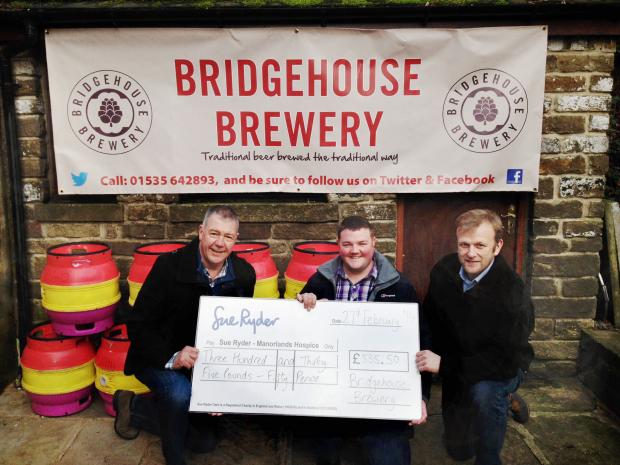 Manorlands fundraiser Matthew Binns, centre, receives a cheque from Bridgehouse Brewery sales and marketing director Simon Lamb, left, and co-owner David Halliday