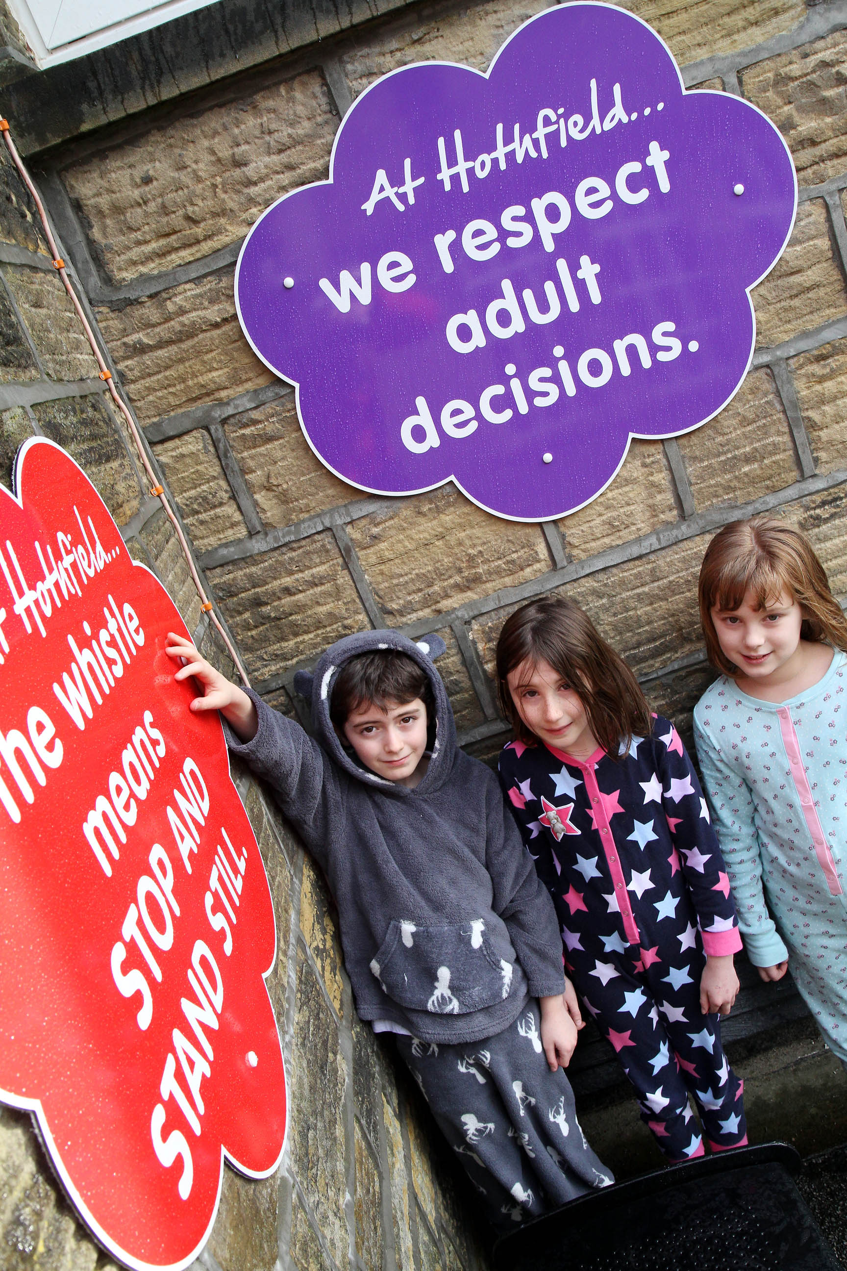 Children from Hothfield Junior School stand by some of the new signs in their playground