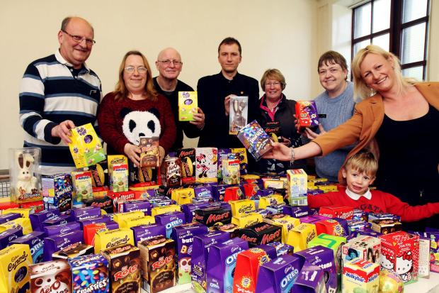 Keighley News: Marcia Dewhirst (right) who organised the Easter egg donations, joins Church of the Nazarene members with some of the chocolate goodies