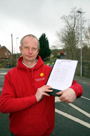Shopkeeper David Mortimer with the petition to build a footpath on Ingrow Lane, which can now be signed online