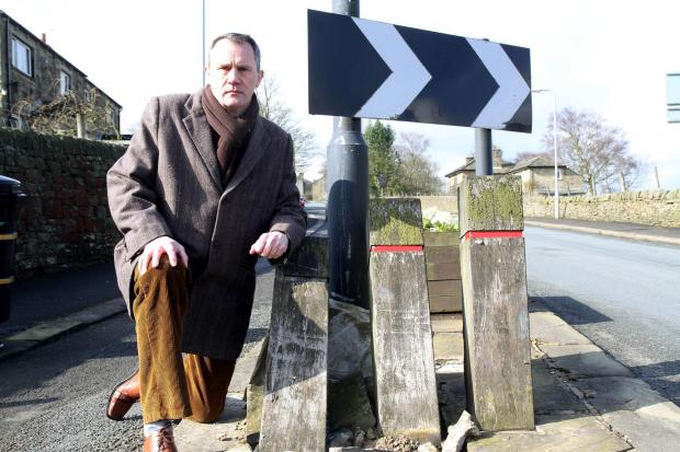 Councillor Glen Miller next to bollards at the entrance to Stanbury, which have been damaged