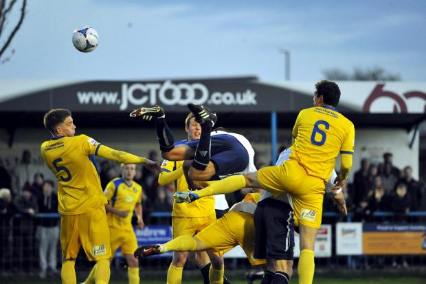 Keighley News: Guiseley's Danny Hall goes flying as he tanngles with the Gainsborough Trinity defence