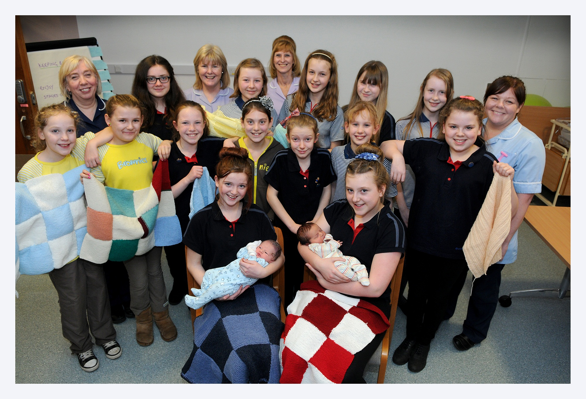 Babies Evan Higgins and Grayson Charlton with Airedale Hospital maternity staff and East Morton Guides, who have knitted patchwork blankets for the unit