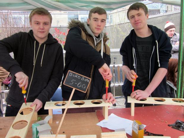Keighley News: Carpentry and joinery level one students from Keighley Campus Leeds City College, from left, Jonny Hardaker, Christopher Hainsworth and Jake Smithurst, demonstrate how to make wooden garden planters and bird boxes