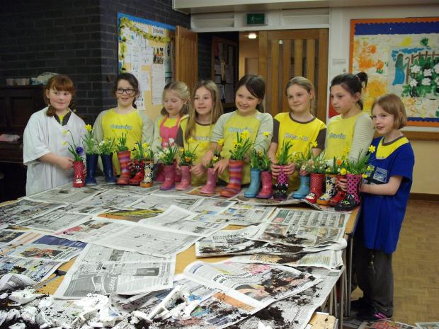 Keighley News: Members of 1st Thwaites Brow Brownies with the wellington boot planters they have created to support Manorlands