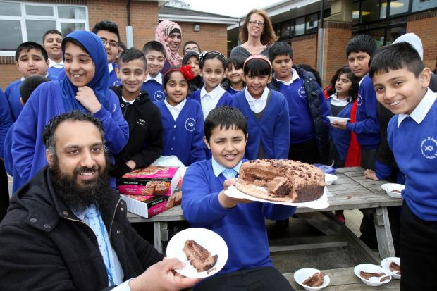 Keighley News: Ibrahim Ahmed, 11, centre, is joined by his uncle, town councillor Amjid Ahmed, fellow pupils and staff during the cake sale at St Andrew's Primary School