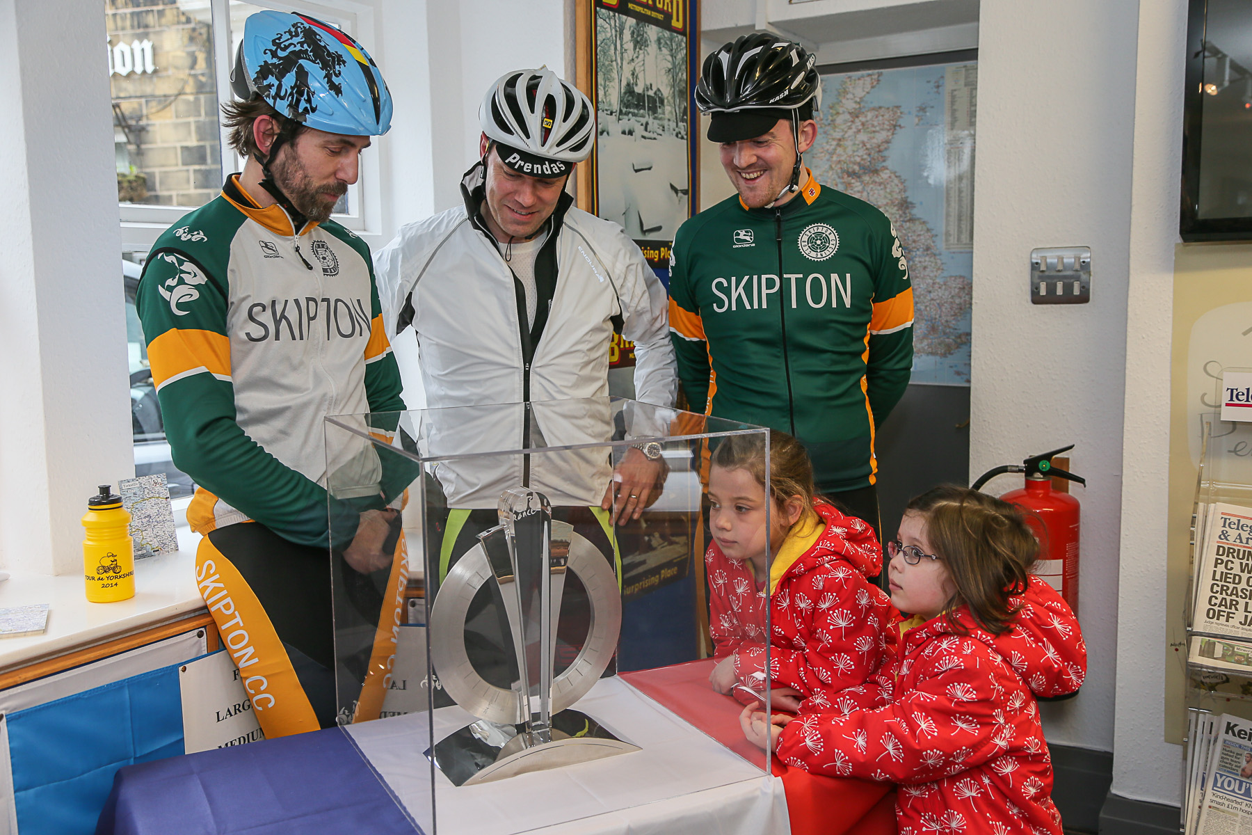 Cyclists Stuart Rider, John Robinson and Luke Mallinder, with children Isobel and Lydia Smalley, admiring the Grand Depart Troph