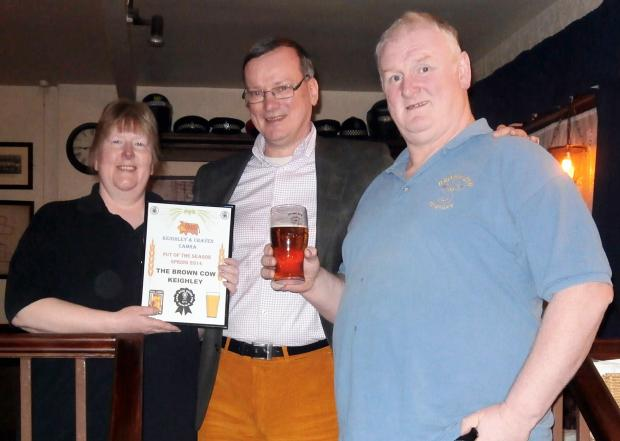 Keighley News: Tony Davies,  centre, of CAMRA, with Carol Taylor-Smith and Barry Smith at the Brown Cow