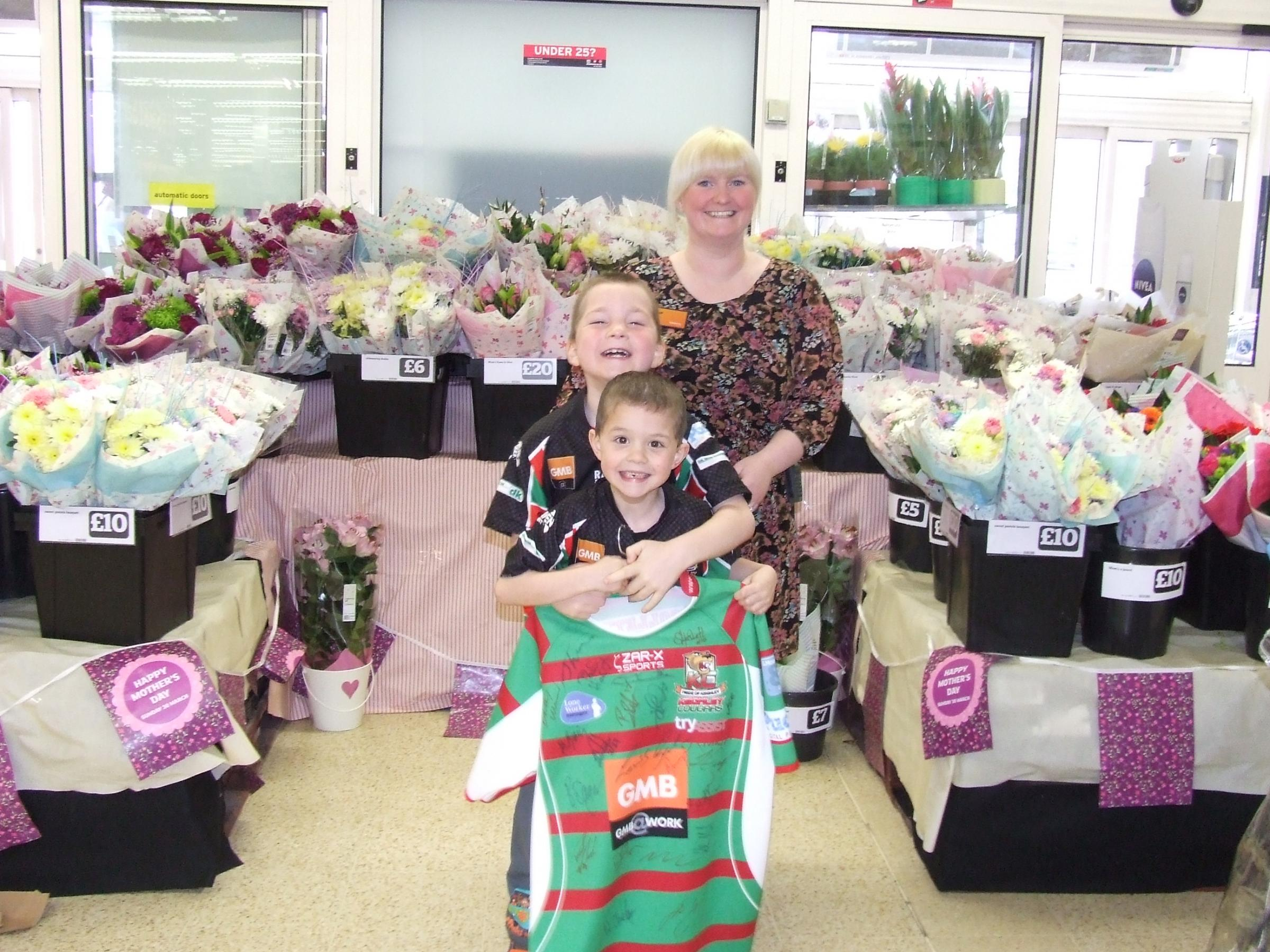 Faye Jessop, deputy manager of the Keighley Sainsbury's store, presenting a Keighley Cougars shirt to raffle winners Bradley and Oliver Foulds