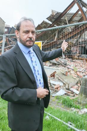 Councillor Abid Hussain (above) standing by the  fire-damaged  building in Lawkholme Lane, Keighley, which has been left to become an eyesore for neighbouring  homeowners