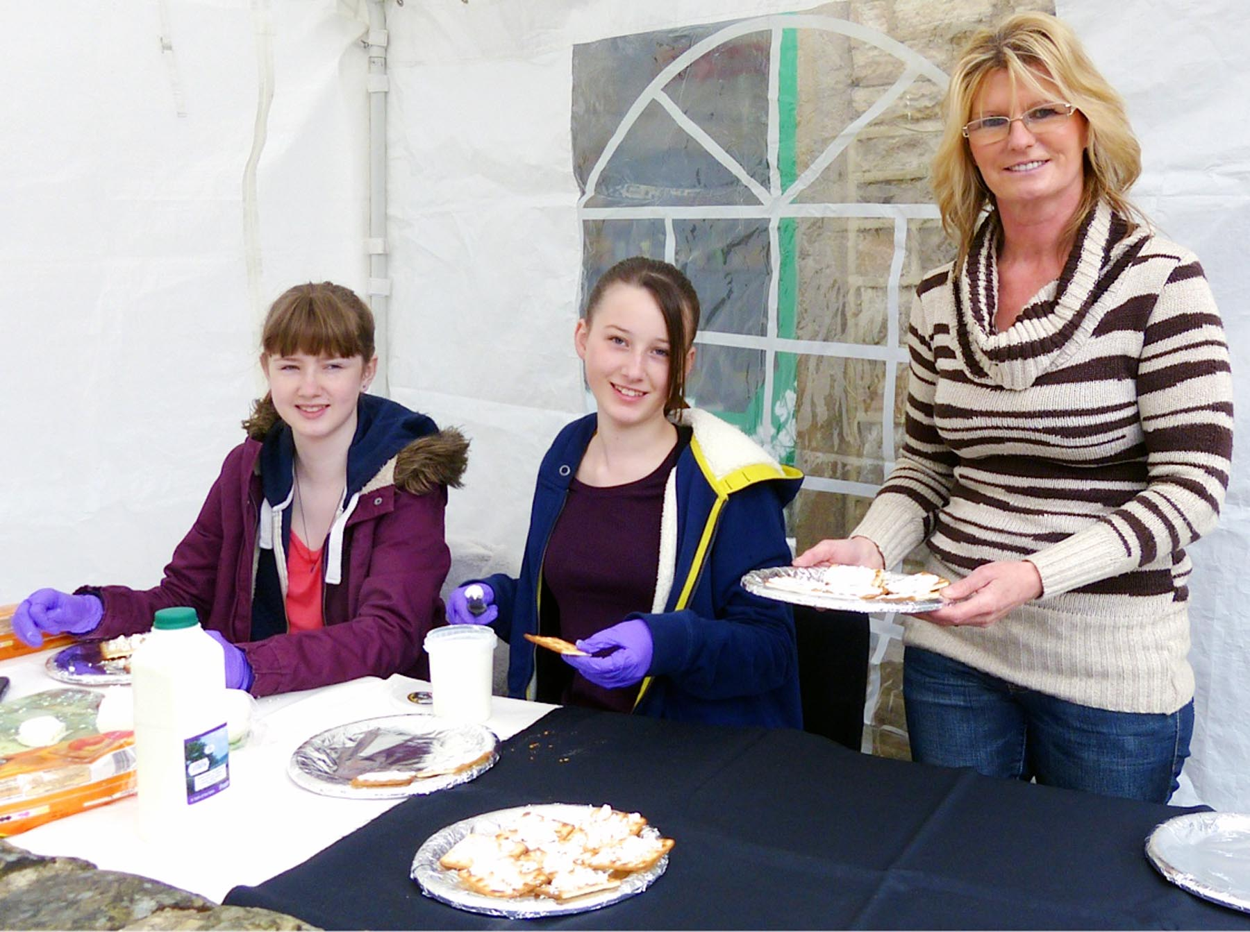 Caitlin Depledge and Georgia Parker, both 13, handing out samples of Yellison Goats Cheese with Sandra Waite, of Bradley Village Shop