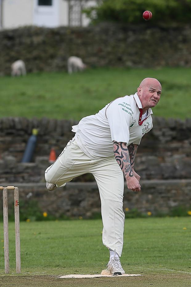 Keighley News: Glusburn's Nick Williamson on his way to six wickets against Bradley