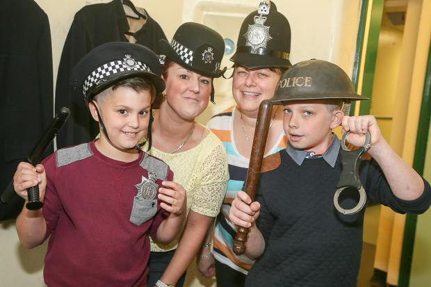 Keighley News: Kalem Ogden, Lindsey Ogden, Adell Esther and Kieran Esther try on some of the uniforms at the Police & Forensic Science Museum in Keighley's Civic Centre