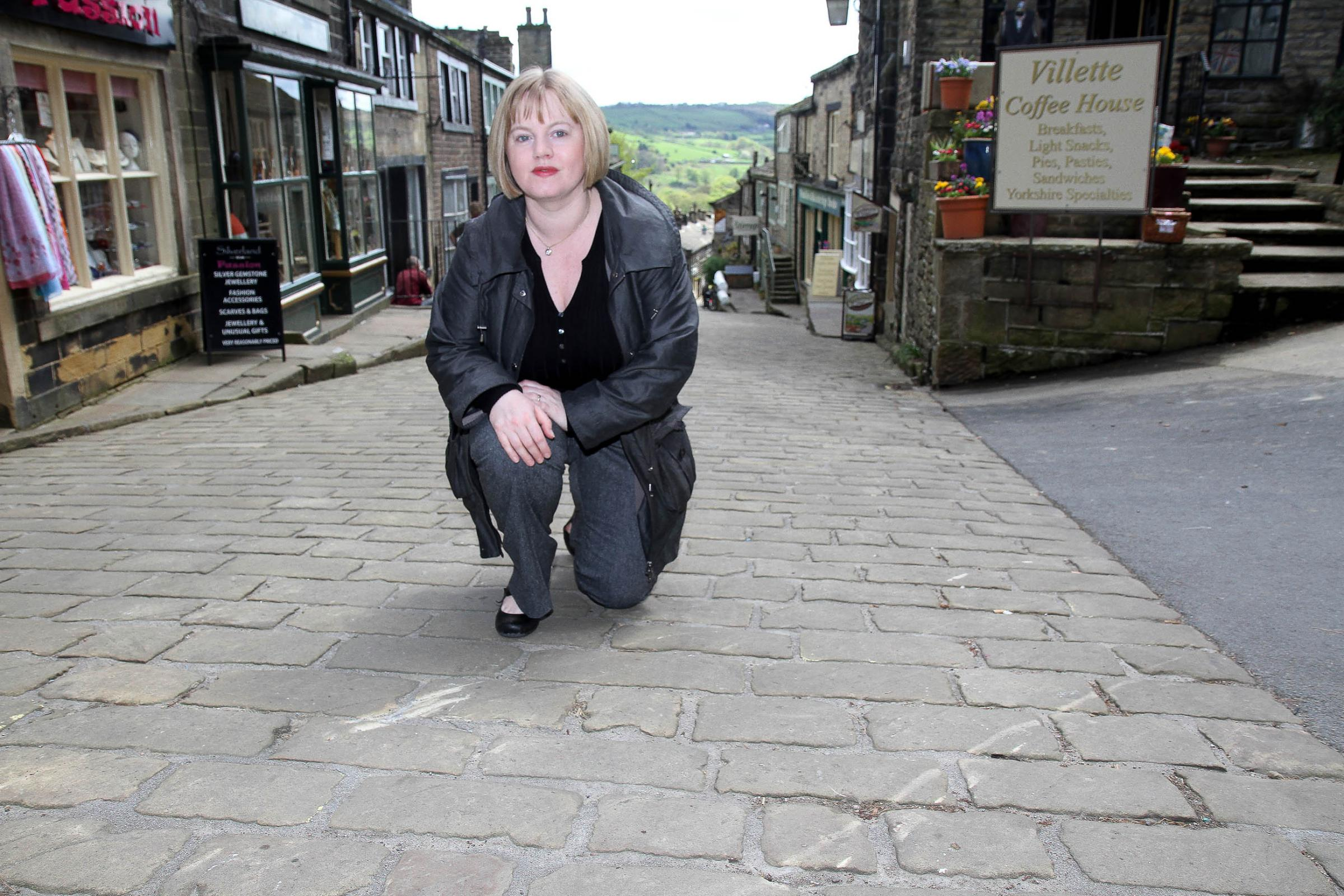 Councillor Rebecca Poulsen in Main Street, Haworth, assessing damage to restored setts allegedly caused by a film crew