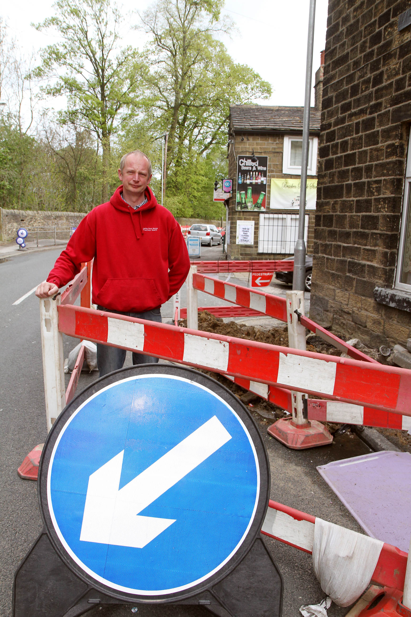 Bracken Bank Stores owner David Mortimer by the roadworks outside his shop and (right) the illuminated figure of a yob caught in the act on CCTV cameras hurling part of the barriers at his building
