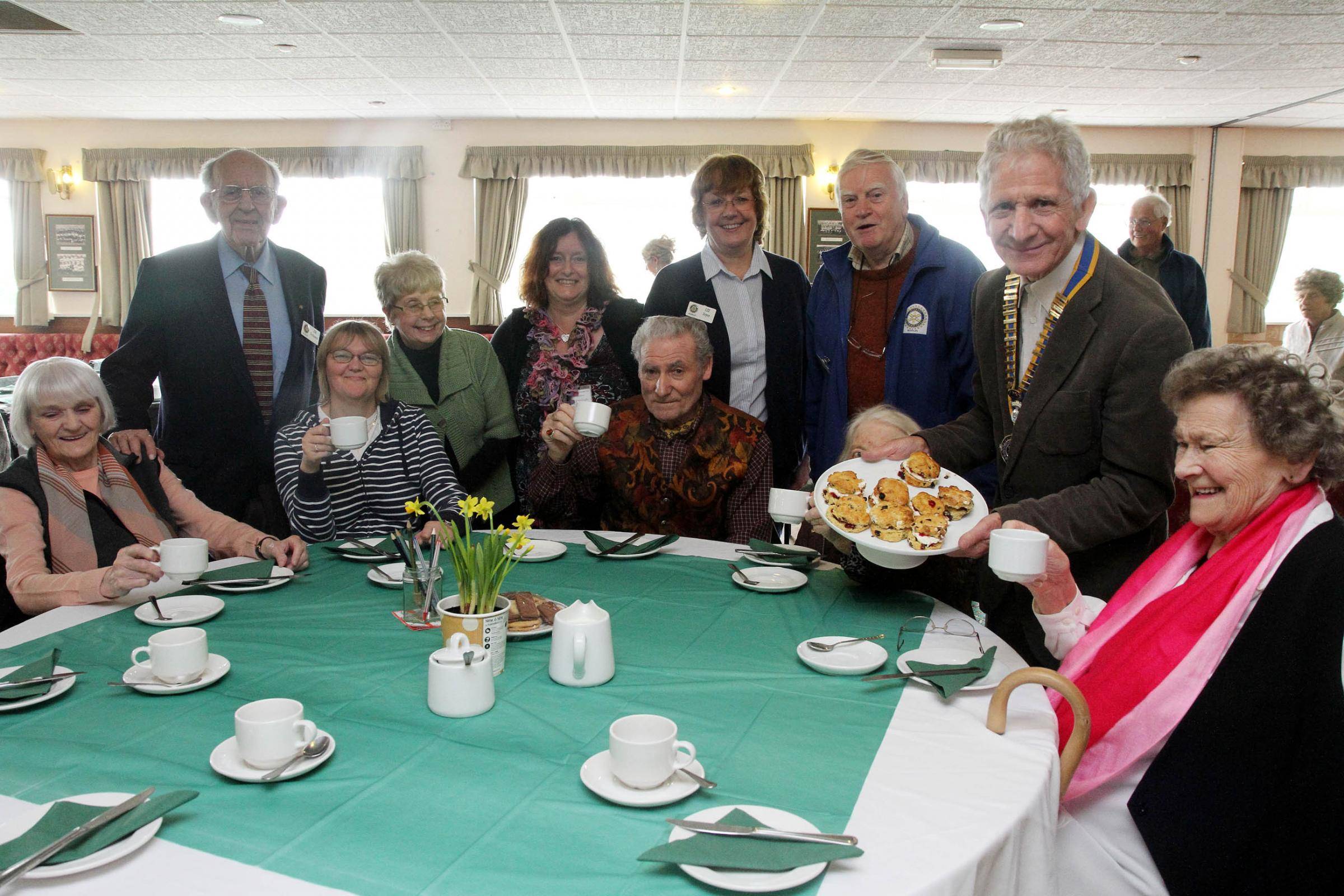 Keighley Rotary president, Alan Hickman (back, right) joins carers and helpers at the afternoon tea event held at Keighley Rugby Union Club