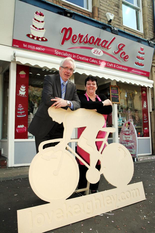 Keighley News: Keighley town centre manager, Philip Smith, with Personal Ice owner, Joanne Smith-Travers, and one of the Tour de France models that will feature in window displays