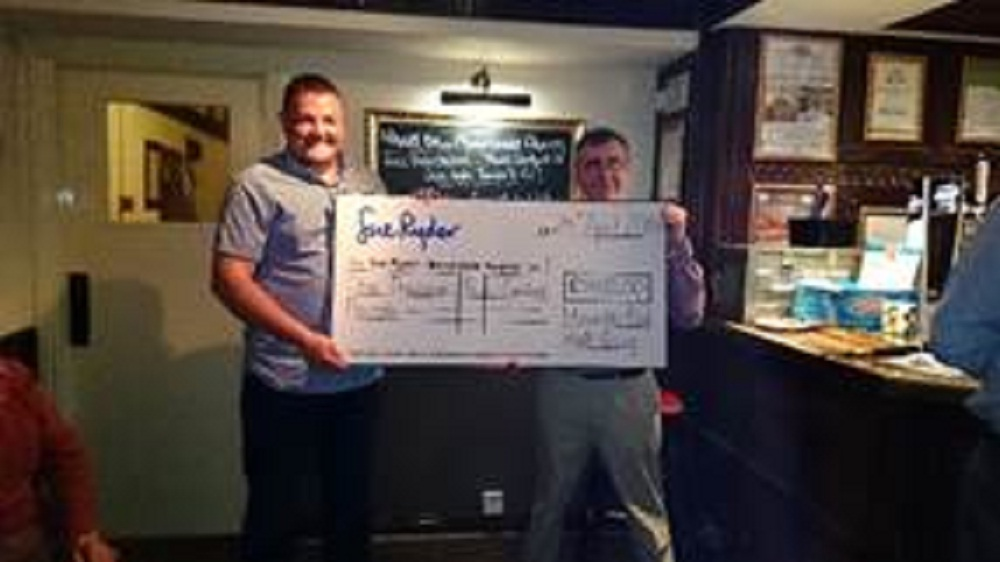 Manorlands fundraiser, Matthew Binns, collects the cheque from David Whitehead at Haworth Old Ha