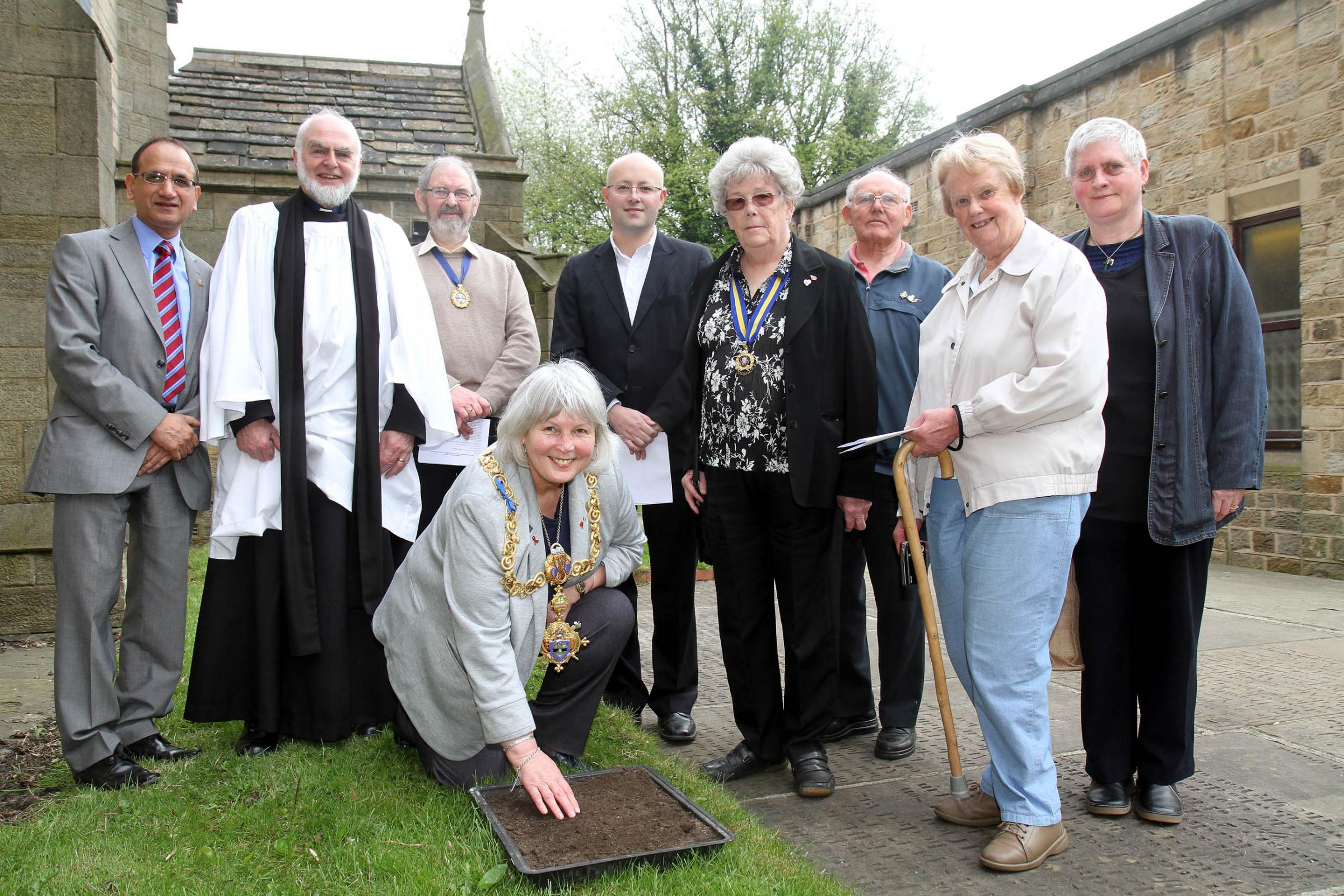 Keighley mayor, Councillor Sally Walkers, sprinkles poppy seeds during the ceremony in Keighley Shared Church yard, with Lord Mayor Councillor Khadim Hussain, left, the Rev Peter Mott and other participants in the memorial event