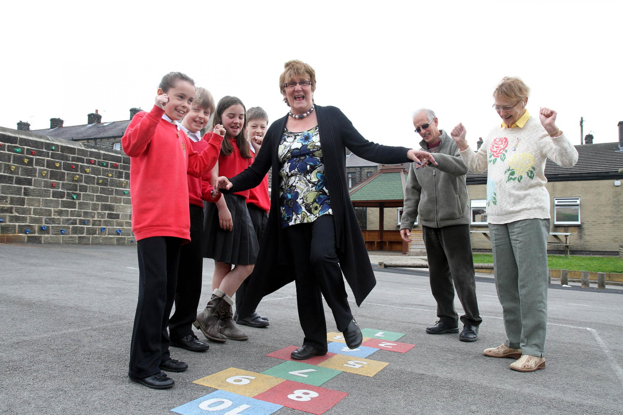 Mavis Clarkson shows off her hopscotch skills watched by visitors Edgar Clarkson and Corrie Sunderland, with Hothfield Junior School pupils, from left, Hannah Griffiths, Ben Walker, Ella Thornber and David Tabszewski