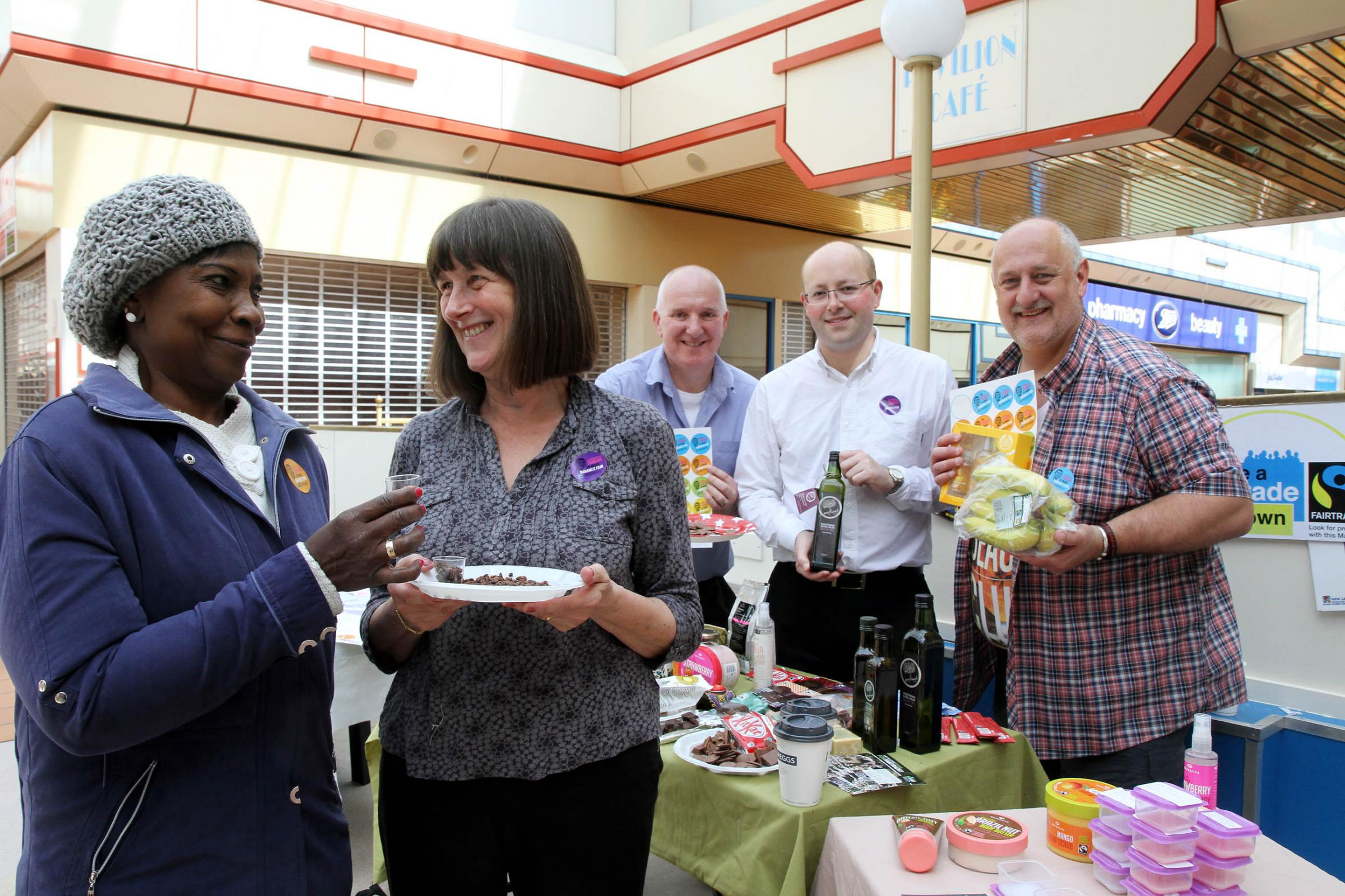 Visitor Yvette Davies, left, samples some Fairtrade food with, from left, Fairtrade volunteers Chris Goddard and Richard Dillon, Councillor Adrian Farley and Airedale Shopping Centre manager Steve Seymour