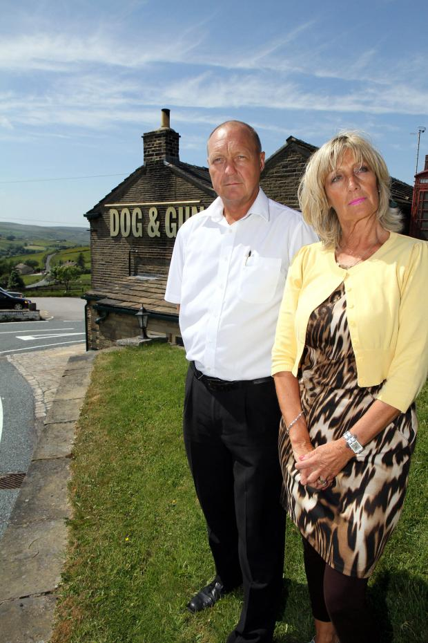 Keighley News: Pub landlord Michael Roper with his wife, Kath, outside their pub, the Dog and Gun in Leeming, Oxenhope