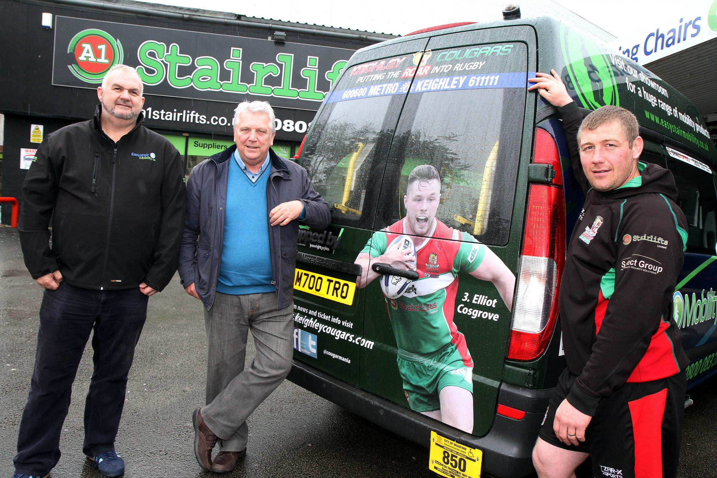Keighley Cougars' head coach Paul March, right, joins A1 Stairlifts' managing director Simon Harrison, left, and Metro Private Hire's Stuart Hastings with one of the vehicles advertising the rugby league team