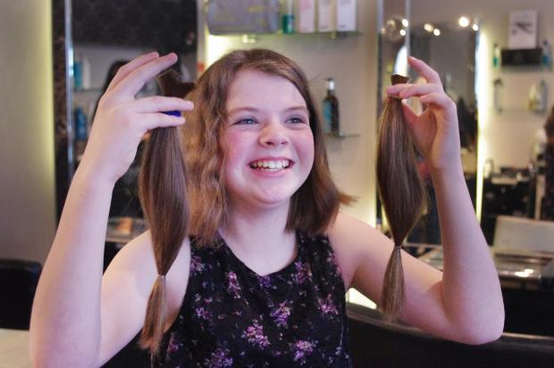 Keighley News: Phoebe Crawford, ten, holding the hair she had cut off to raise funds for the appeal to help cancer sufferer Callum Ingham