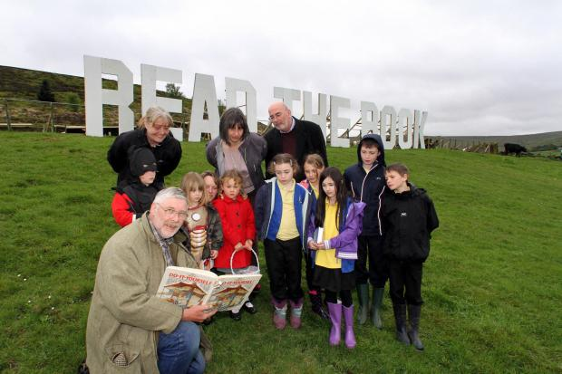 Children and staff from Oldfield and Haworth primary schools are joined by the Reverend Mick Lockwood, minister at Hall Green Baptist Church, with Councillor Russell Brown at the new Read The Book sign