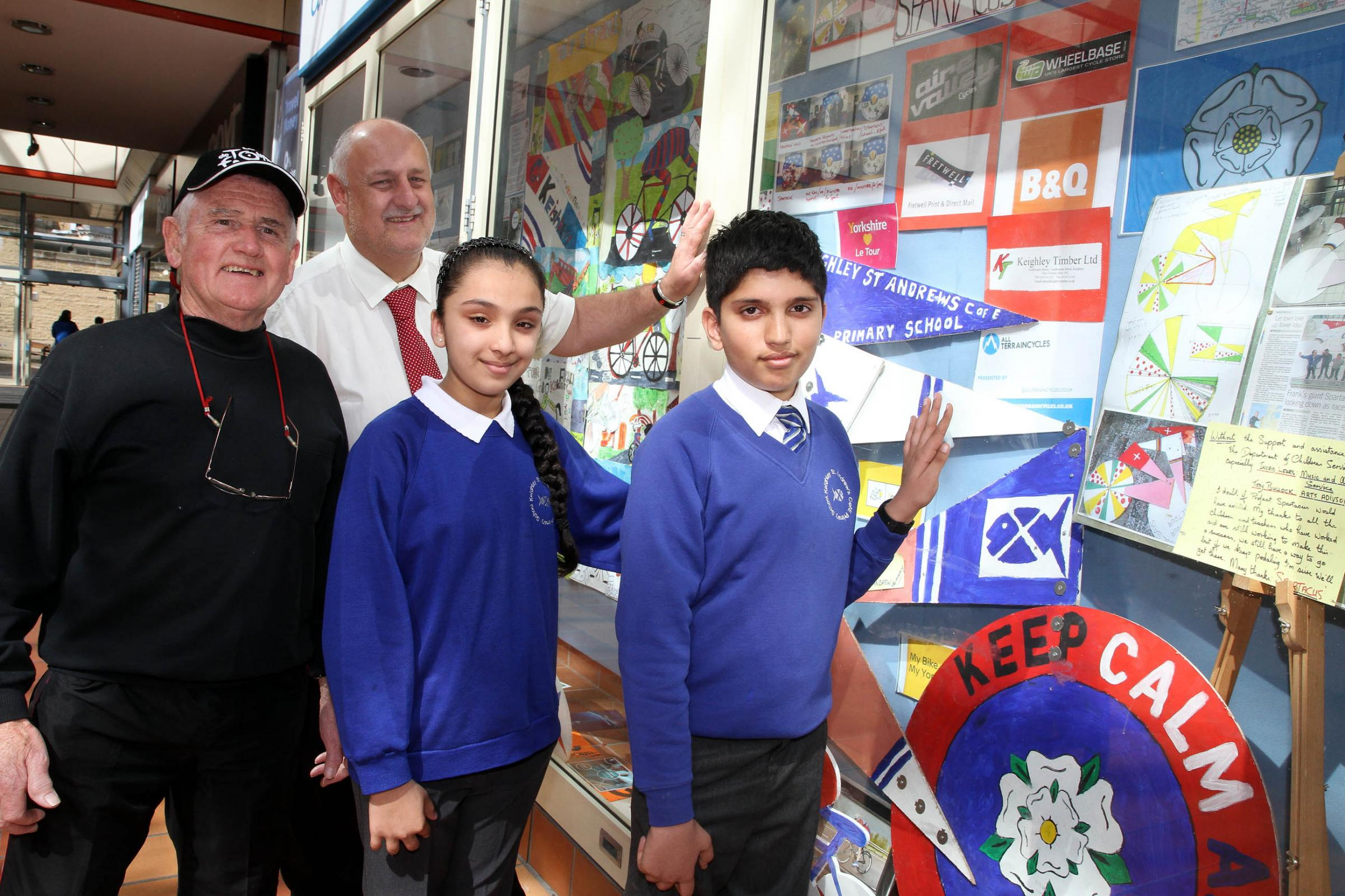 Frank O'Dwyer, left, joins Airedale Shopping Centre manager Steve Seymour and St Andrew's Primary School pupils Halina Mahmood and Bilal Sharif at the Tour de France Grand Depart display