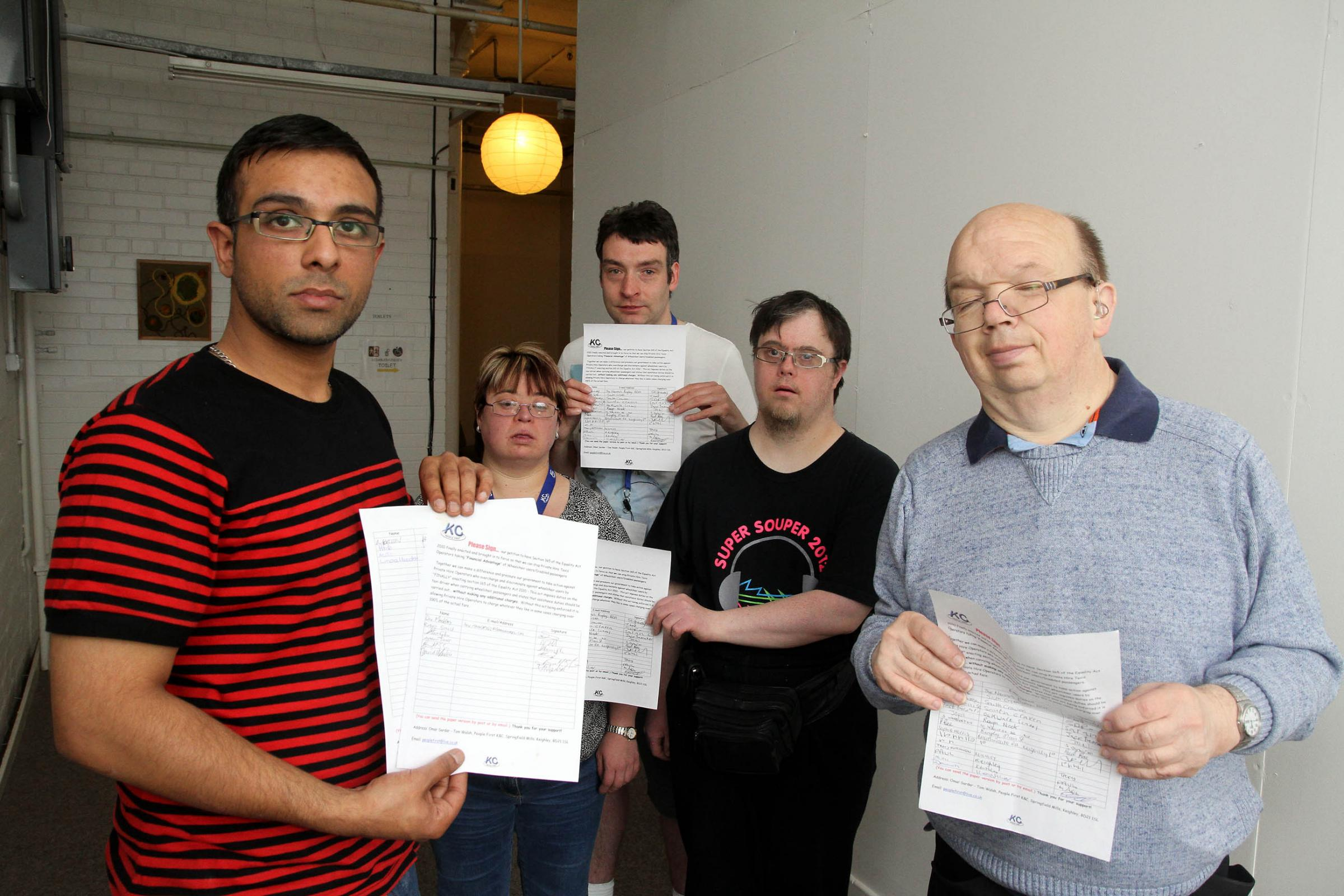Members of People First, from left, Omar Sardar, Sarah Clapperton, Adam Parke, Stephen Whiteside and Tim Pickles with copies of the petition calling for fair taxi fares