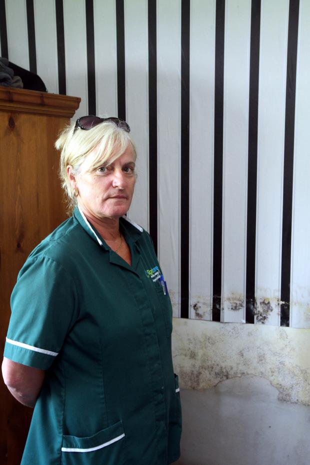 Keighley News: Julia Reeder in one of the bedrooms in her home blighted from damp walls, which has ruined her possessions