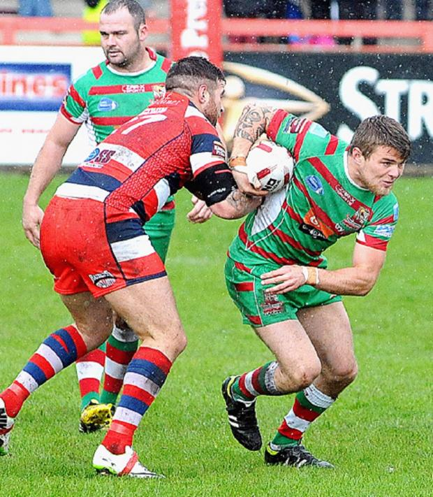 Keighley News: Cougars interchange Jack Lee drives forward in the rain