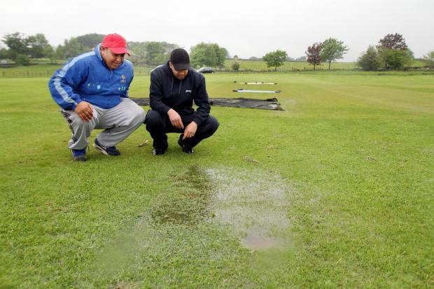 Wasim Hussain and Nadeem Safdar inspect the waterlogged pitch at Ingrow St John's, where their match against Embsay was one of virtually all that fell victim to the heavy Saturday rain
