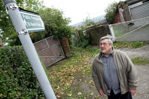 Keighley town councillor, Peter Corkindale, by the blocked footpath in Becks Road, which is now the subject of action by Bradford Council to re-open the route