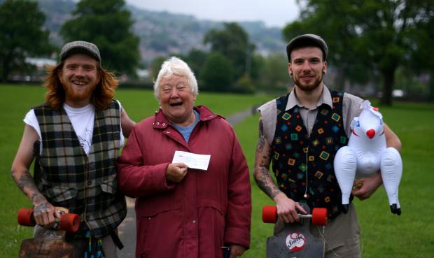 Johnny Phillips, left, and Michael Laidler, right, receiving a cheque from Jean Harper, whom they met in Victoria Park during their charity skateboarding challenge to raise funds for the Children's Heart Federation