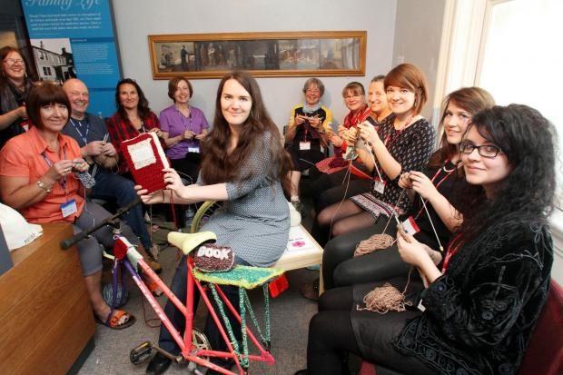 Keighley News: Cassandra Kilbride, centre, is joined by knitters in the woolly bike workshop at the Parsonage Museum, part of the Yorkshire Festival 2014