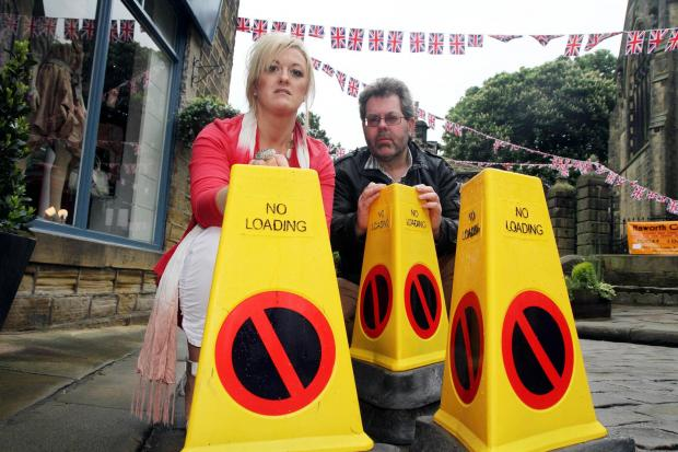 Nikki Carroll and Andy Kissack, of Haworth 1940s Weekend, with four of the no-parking cones returned, leaving more than 150 still missing