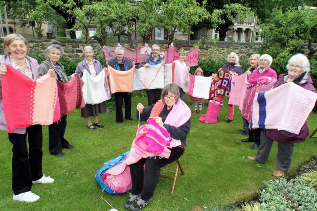 Participants gather at Keighley Quaker Meeting House to help knit some of the segments of the giant pink peace scarf