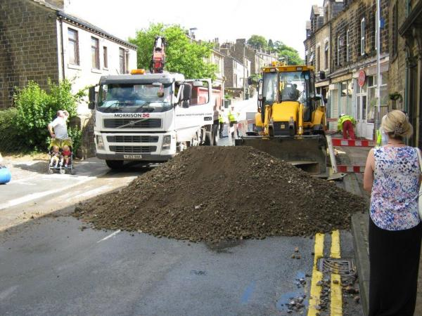 Workmen begin to fill the crater in Oakworth with soil after the road collapsed following a burst water main