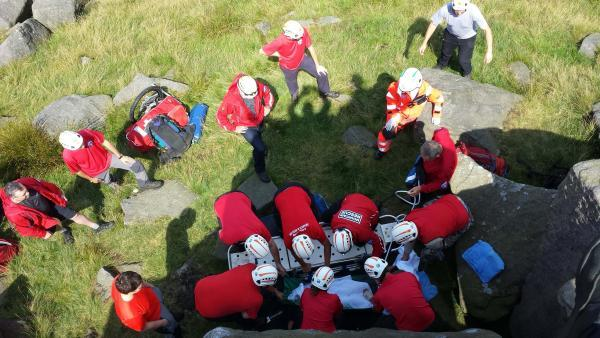 Members of the rescue team lifting the injured climber onto a stretcher