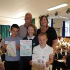 Keighley News: Cowling Primary School pupils Harry Rowe, Mollie White, and Holly Whitaker had the winning designs of a poster competition highlighting the issue of dog fouling. Village lengthsman David Hitchcock and Rachel Jackson, chair of the Recreation Ground Managem